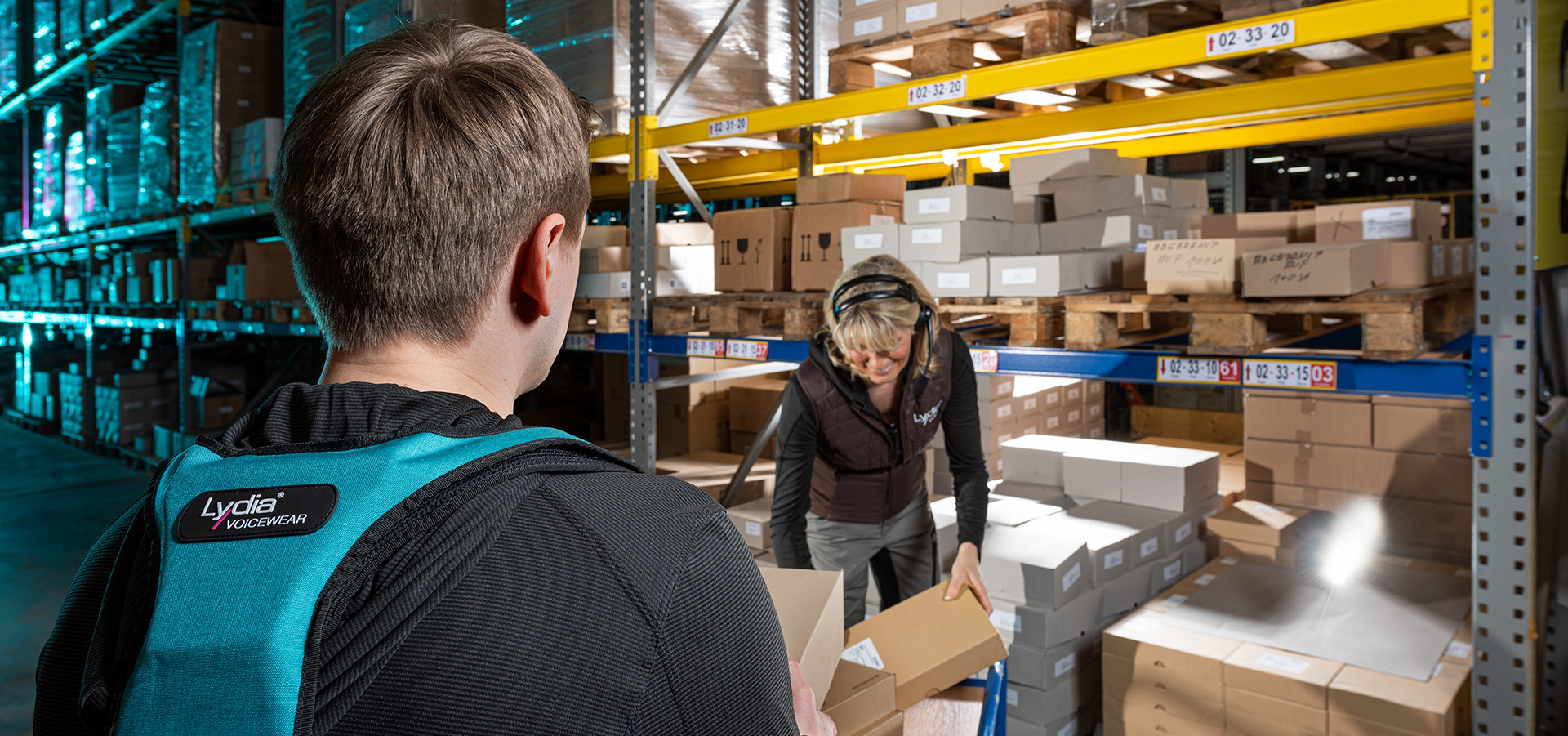 A warehouse employee gives a package to another warehouse employee, both of whom carry Lydia Voice devices.