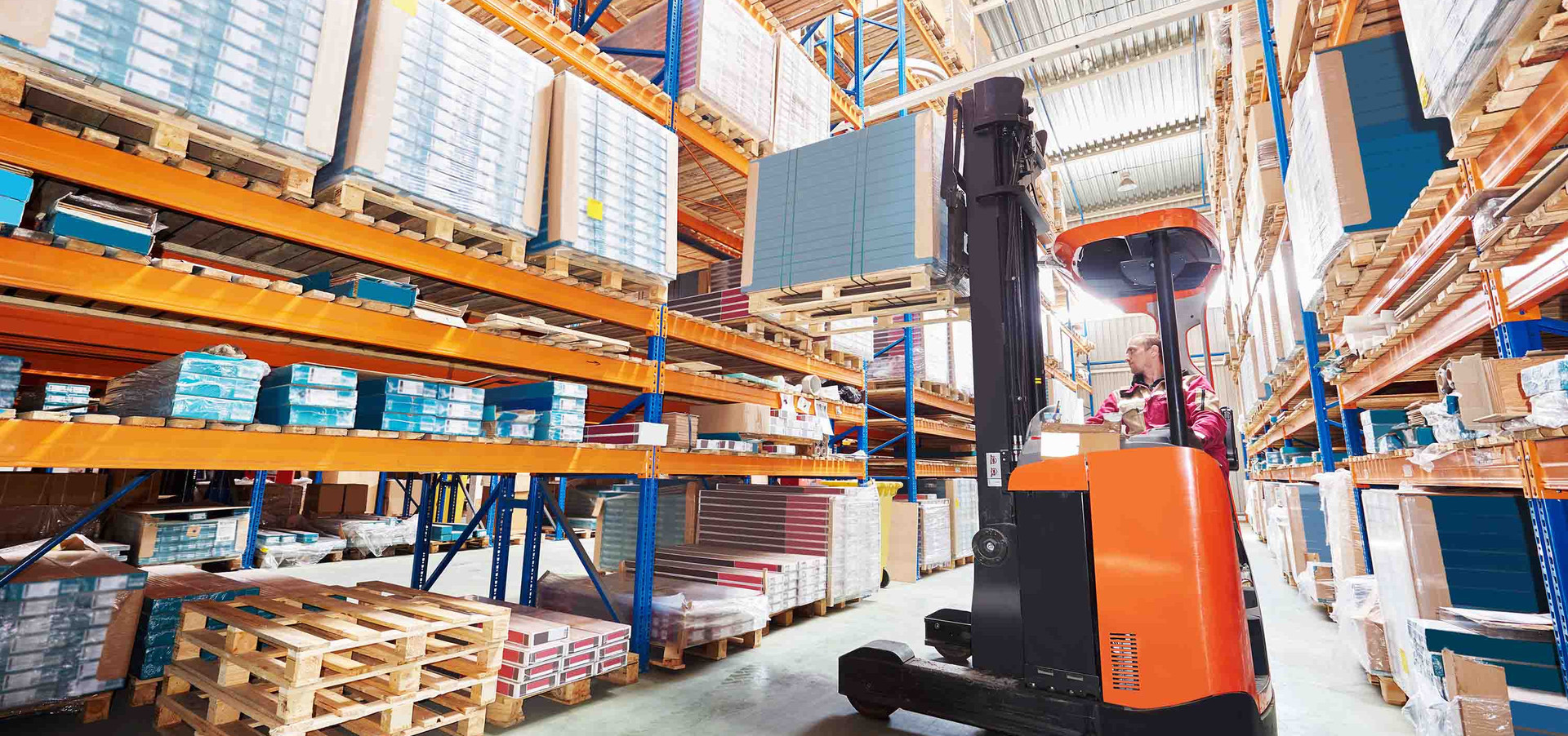 A forklift lifts a pallet from a storage rack on instruction by our software LFS.wms.