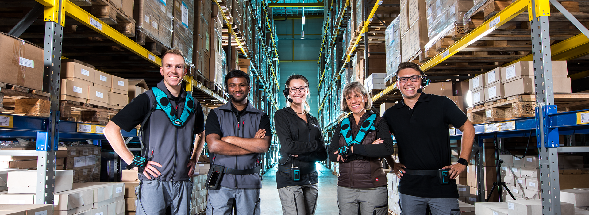 The picture shows five warehouse workers which are working with Lydia voice devices.