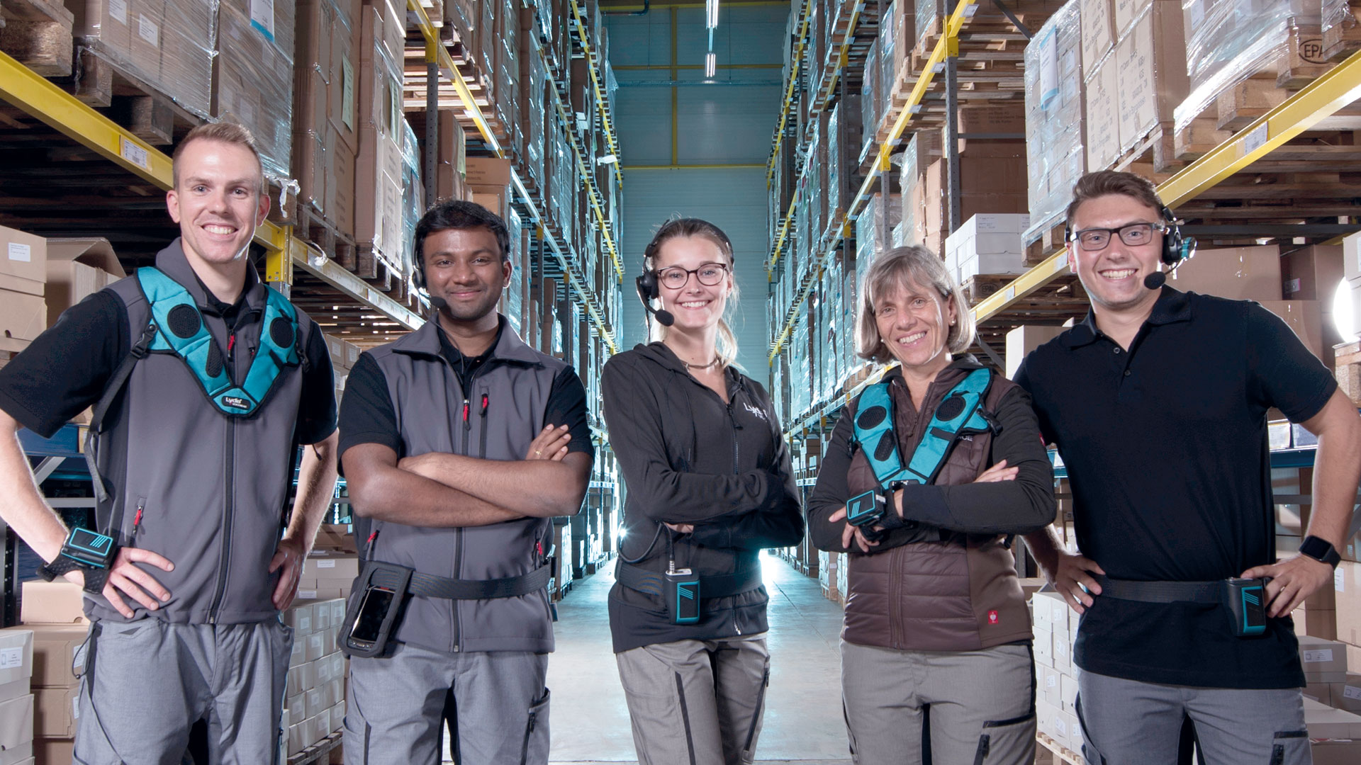 Several warehouse employees stand between storage racks and present different warehouse equipment such as Lydia VoiceWear, headsets, scanners and mobile devices that work with Lydia Voice.