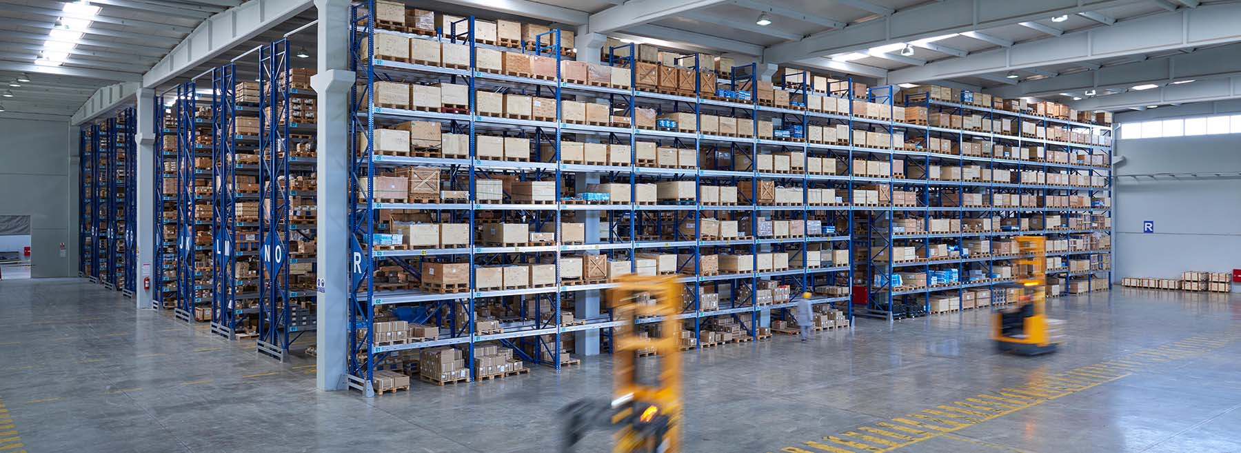 The picture shows a warehouse with several rows of high shelves. Two forklifts pick with the help of our warehouse management system LFS.wms in the warehouse.